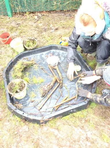 Gathering materials for a mud hut with a wooden structure