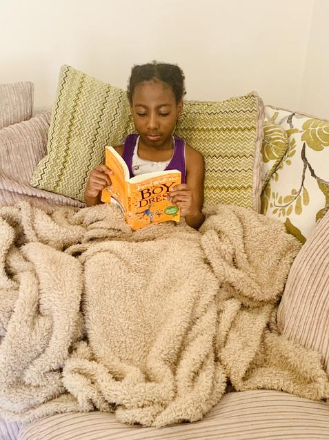 Tolu snuggled up under the blankets to read
