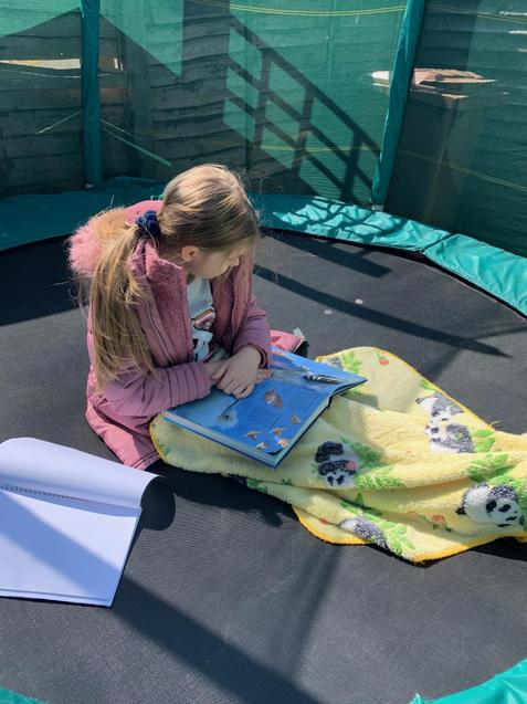 Milana's making use of the trampoline to read