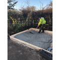 Simon rakes the concrete to form the base