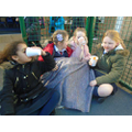 Year 2 girls keeping warm at their shelter, eating