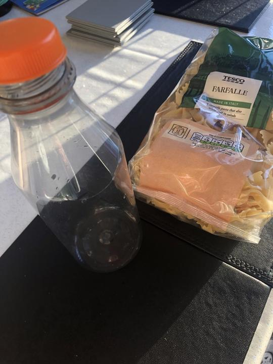 a bottle half filled with pasta