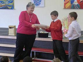 Rowan and Jacob present Mrs Aulton with flowers