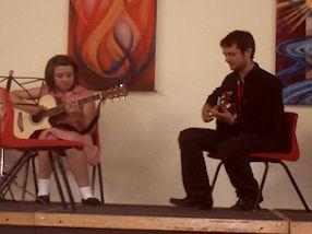 A pupil playing a duet with her guitar tutor.