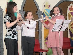 Playing the flutes, with their tutor.