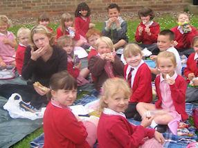Staff and pupils enjoying a picnic on the grass.