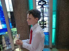 Entering with his Communion candle.