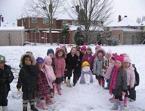 Happy, proud children with their snowman.