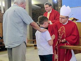 One of the boys gets anointed by the Bishop.