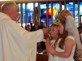 Children receiving Jesus in Holy Communion.