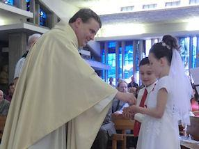 Children receiving Jesus in Holy Communion.