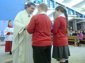 Pupils bring the Offertory Gifts to the altar.