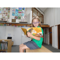 Elf on the shelf reading a story in the library