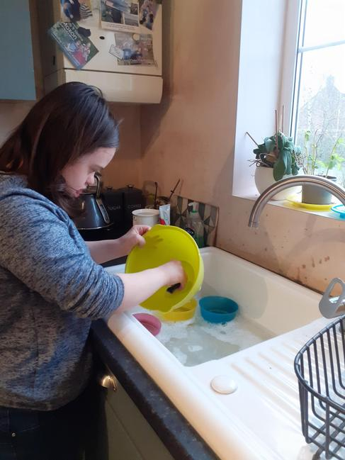 Freya is washing her pots after baking.