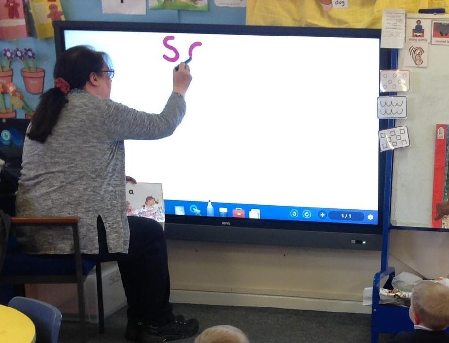 Nursery teacher modelling letter formation