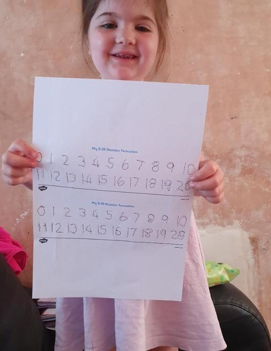 Practising her number formation...