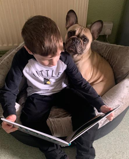 Oscar was comfy reading to his dog!