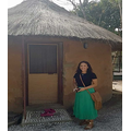 Take a photo outside a traditional African hut