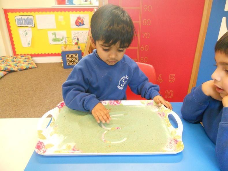 Practising forming letters in sand,