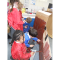 Reception children busy painting the Endeavour