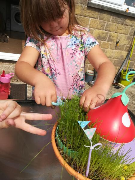Erin cutting her fairy garden grass.