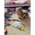 Y1 reading to little sister and her toys