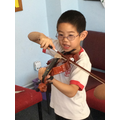 Using the bow for the first time during a violin lesson.