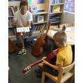 A chid practicing his strumming patterns.