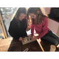 Sisters playing their senet boardgame