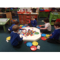 Sorting larger objects by their primary colour using tongs.