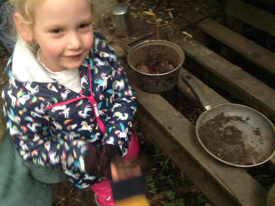 Making 'hot chocolate' in the mud kitchen.