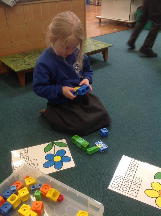 ...Using multi link cubes to create a flower by following a pattern sheet.