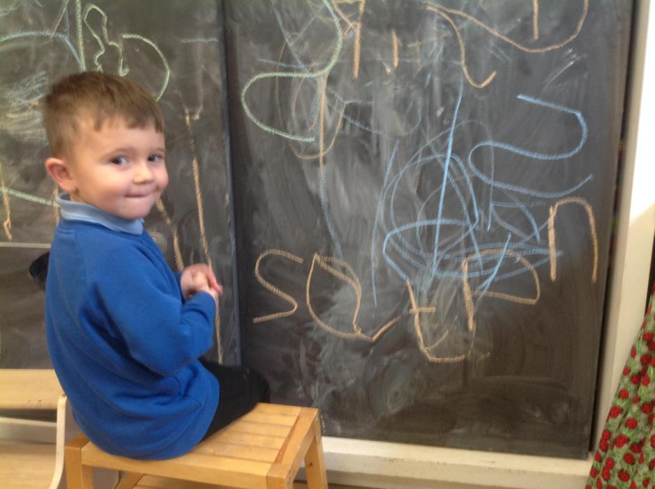 Practising letter formation on the blackboard...
