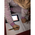 Evie-Rose watching the phonics lesson and writing the words.