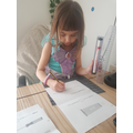 Emilia using her ruler to measure the objects