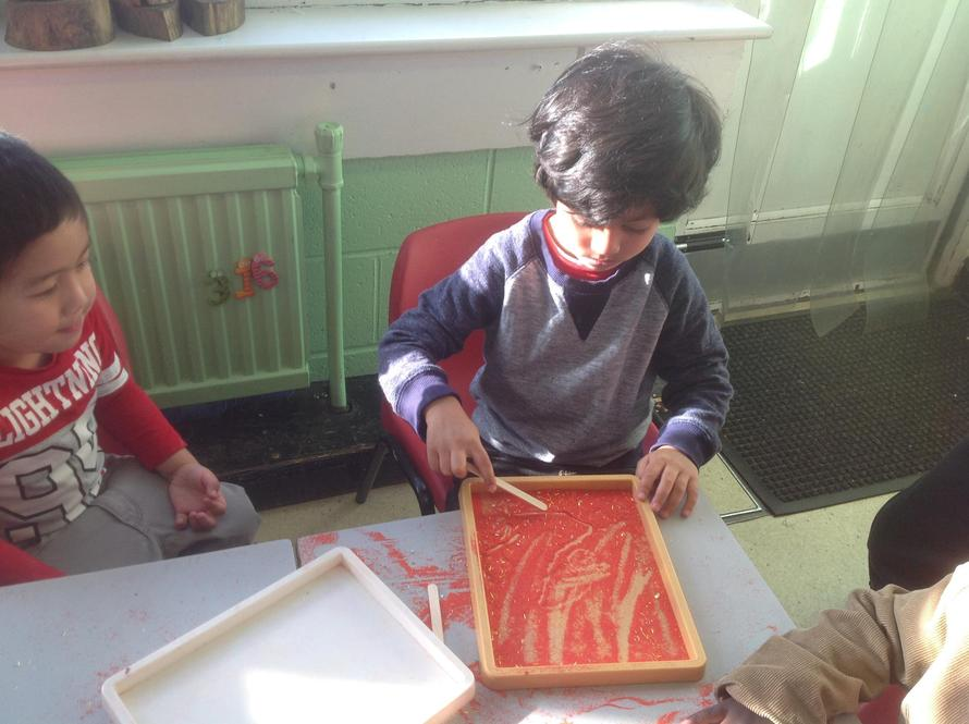 We practised writing chinese script in sand trays.