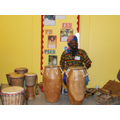 Kwame surrounded by drums playing in Yellow class
