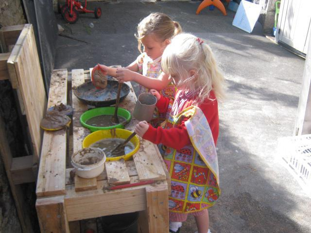 Mixing muffins and cookies in the mud kitchen