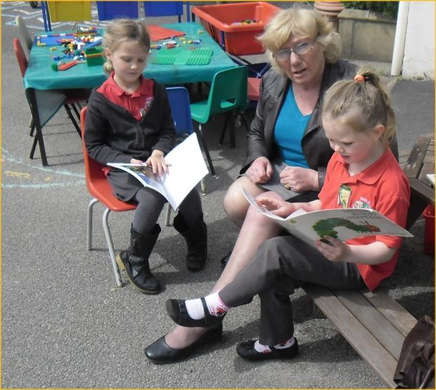 Rowan and Xanthe read a book to their Grandma