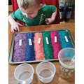 Hughie has been colouring rice, naming the colours and looking at the changes.