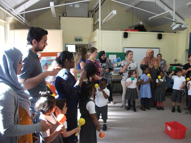 Nursery enjoy a music session with their parents.