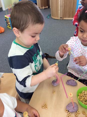 Using playdough and threading through cherrios