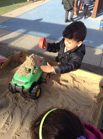 We are learning to pour, fill and empty in the sand pit