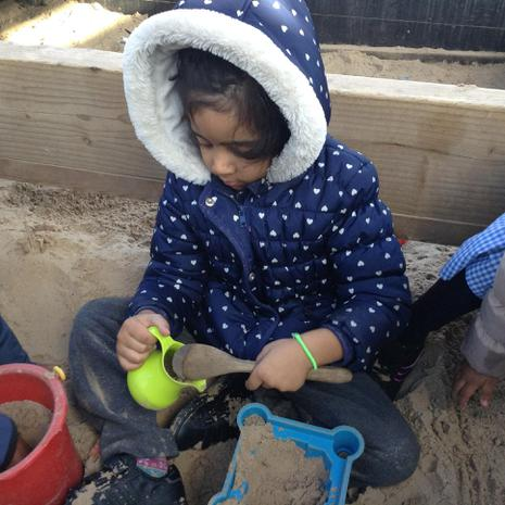 We are learning to dig and pat in the sand areas