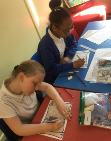 Here are the children creating a 'Come and see our play' poster.