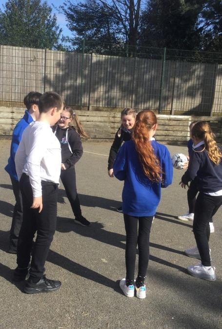 Year six children demonstrating teamwork in their P.E lesson.