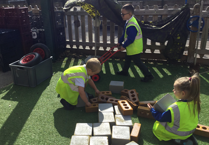 Making a car together in the outdoor classroom using different loose parts.
