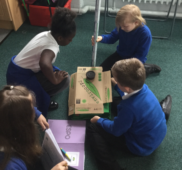 Year 4/5 completing their Science experiment about forces and the different surfaces.