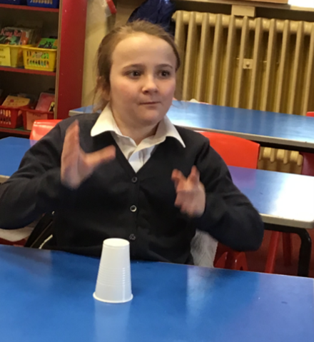 Music lesson; pulse and rhythm expressed through clapping whilst using a cup.