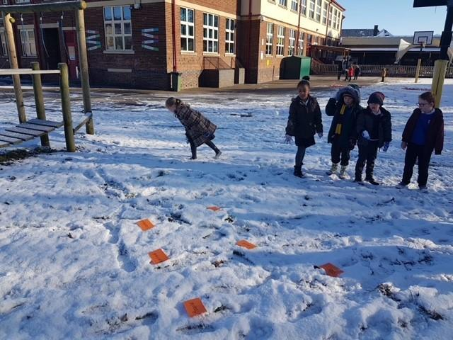 Phonic games in the snow, finding tricky words and throwing snow balls at them